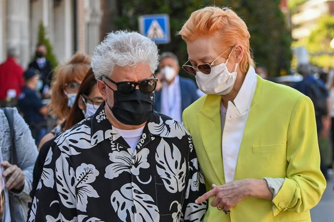 Spanish director Pedro Almodovar (L) and British actress Tilda Swinton, both wearing a face mask, leave the Excelsior Hotel on their way to attend a photocall for the film 'The Human Voice' presented out of competition on the second day of the 77th Venice Film Festival, on September 3, 2020 at Venice Lido, during the COVID-19 infection, caused by the novel coronavirus. (Photo by Alberto PIZZOLI / AFP)