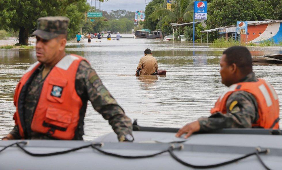 San Pedro Sula ha sido una de las zonas más afectadas por el paso de Iota en Honduras. El río tras el Chamelecón se desbordó este miércoles. En la imagen, un hombre cruza una calle inundada mientras dos soldados asisten a los afectados con una lancha.