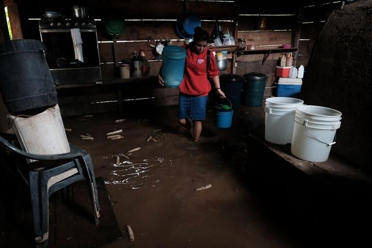 Una mujer evacúa su hogar en la comunidad El Guineo en Suina, ante las inundaciones provocadas por el huracán Iota.