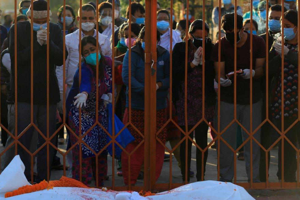 Familiares de víctimas de la covid-19 lloran por la muerte de sus seres queridos, a las puertas de un crematorio de Katmandú (Nepal).