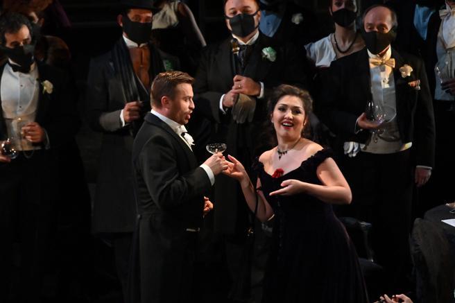 El coro del Liceu, que usaba mascarilla, en el momento del brindis con Alfredo y Violetta en primer término .
